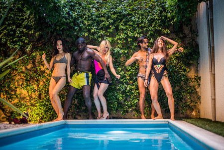 Multi-ethnic group of friends in a swimming pool - Young happy people having fun and enjoying summertime in a aquapark Stock Photo