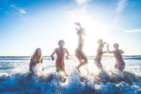 multi-etnico gruppo di amici che saltano sulla spiaggia - Giovani che hanno divertimento in mare durante le vacanze estive photo