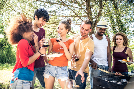 Happy multiracial friends having fun at picnic barbecue garden party Stock fotó
