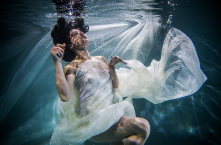 Beautiful woman swimming underwater with elegant dress Stock Photo