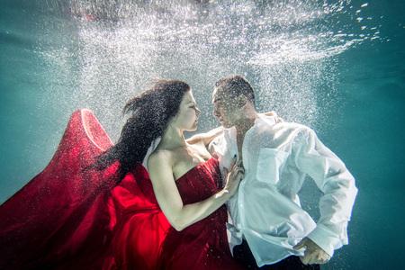 美しいドレス - 芸術的な夢のような肖像画を持つ水中水泳のカップル