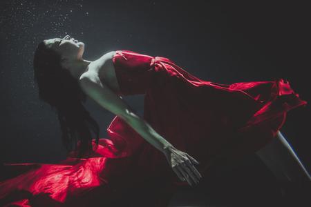 エレガントなドレスと水中泳いでいる美しい女性