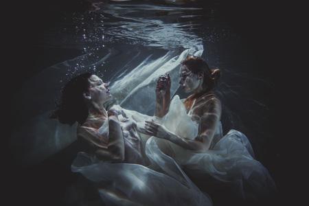 Beautiful women swimming underwater with elegant white dress