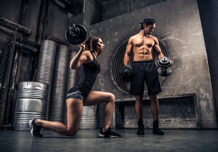 Athletes training with weights in a gym - Functional training workout