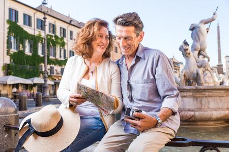 Senior couple at Navona square, Rome - Happy tourists visiting italian famous landmarks Stock Photo