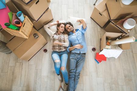 Pareja mudándose a un nuevo hogar: las personas casadas felices compran un nuevo apartamento para comenzar una nueva vida juntos