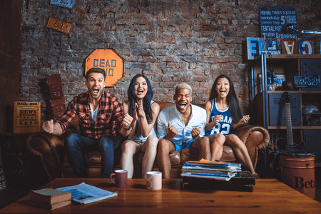 Mixed race group of teenagers having fun on the couch - Multi-ethnic young adults partying at home Foto de archivo
