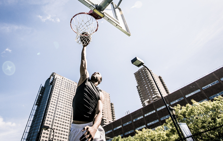 Basketball player making huge slam dunk 版權商用圖片