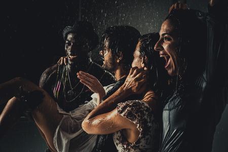 Groep vrienden die in de regen dunken