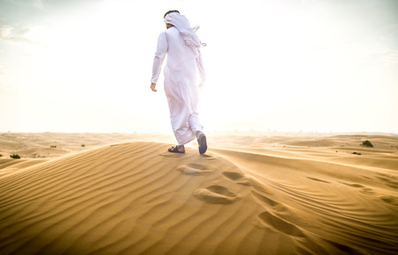 Arabic man with traditional emirates clothes walking in the desert Stock Photo