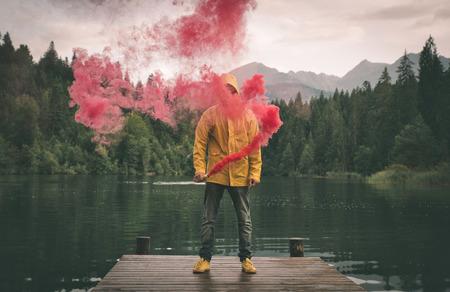 Man standing on the lake walkway with smoke bomb