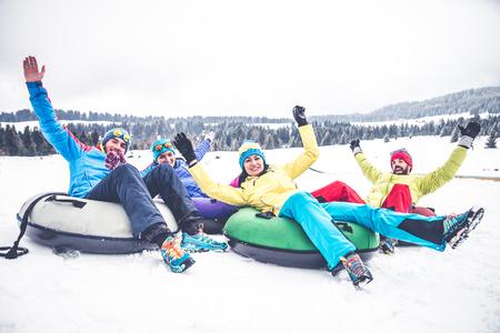 冬の休日 - 雪の上スライドに乗ってスキーヤーのスキーと友人のグループ 写真素材
