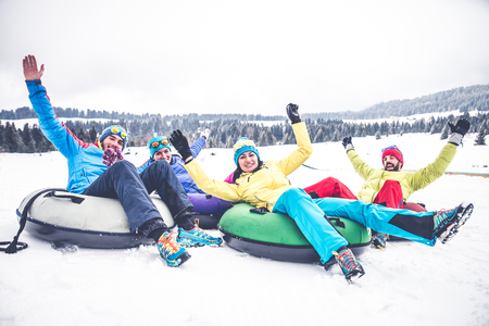 Group of friends with ski on winter holidays - Skiers riding on slides on the snow Stock Photo