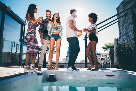 Grupo de amigos que se divierten en la azotea de un hermoso ático