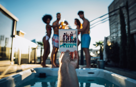 man drinking water: Group of friends having fun on the rooftop of a beautiful penthouse Stock Photo