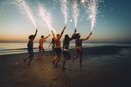 Group of friends having fun running on the beach with sparklers