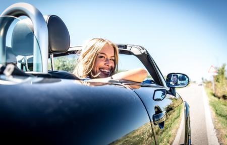 Couple driving on a convertible car and having fun Foto de archivo