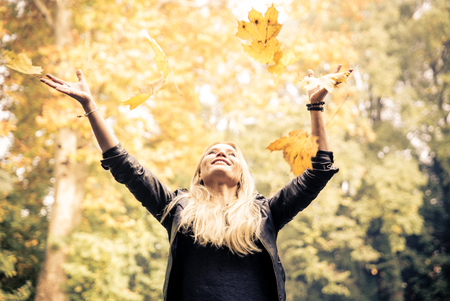 Woman in a park throwing yellow leafs in the air Stok Fotoğraf