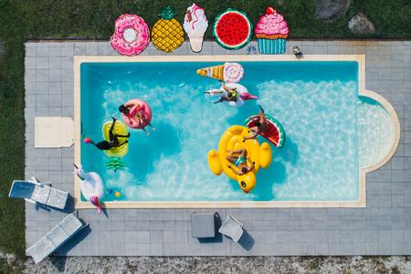 Groep vrienden plezier in het zwembad met verschillende lucht bedden