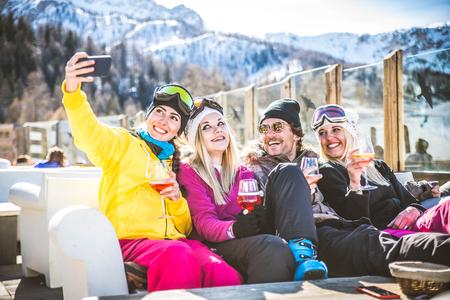 Groep vrienden praten en plezier hebben in een buitenrestaurant op de wintervakantie