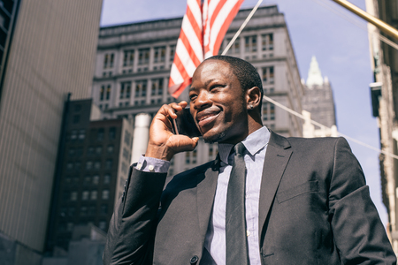 Businessman speaking at cellular phone outdoors