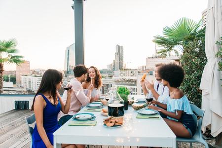 屋上でパーティーを持つ友人の多民族グループ - 幸せな人々の絆と楽しみを持っています