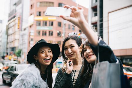 도쿄에서 시간을 보내고 도시의 다른 지역에서 쇼핑하는 일본 여성들의 그룹 + 스톡 콘텐츠