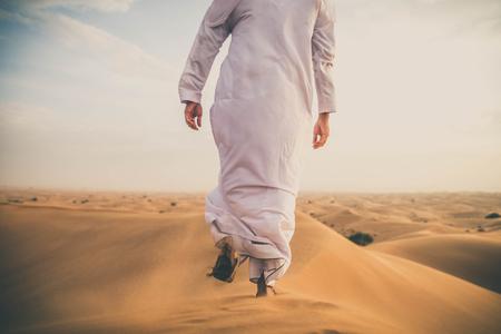 日の出の砂漠を歩くアラビア人男性