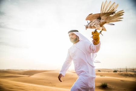 Arabian man walking  in the desert at sunrise 版權商用圖片 - 90911111