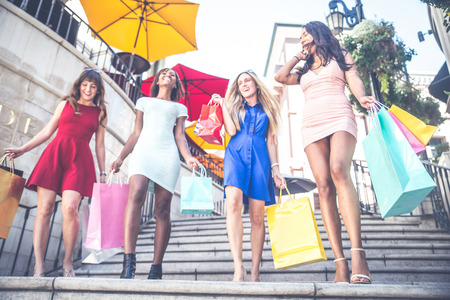 Multiethnic group of girls shopping - Four beautiful woman having fun while buying some presents in a mall Stock Photo