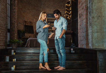 Couple at home with smartphone having conlicts in their relationship