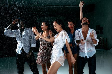 Groep vrienden die onder de regen dansen - Multi-etnische mensen die partij hebben Stockfoto