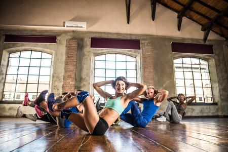 ジムでトレーニングする多民族グループ - フィットネスクラスのパーソナルトレーナーとスポーツマン