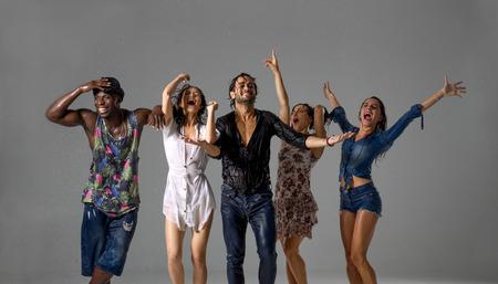 Gruppe Freunde , die unter dem Regen tanzen - multiethnische Leute , die Party tragen