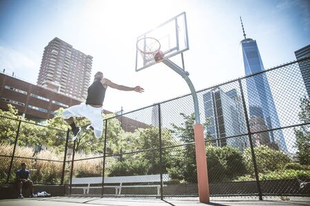 Afroamerican athlethe playing basketball outdoors - Basketball player dunking on court in New York Stock Photo