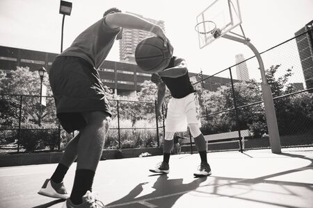 Two afroamerican athlethes playing basketball outdoors - Basketball athlete training on court in New York Imagens