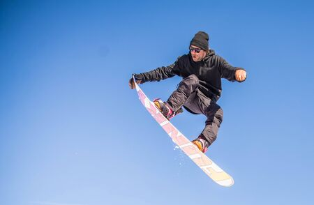 Snowboarder performing tricks on the snow with dramatic background Stock Photo