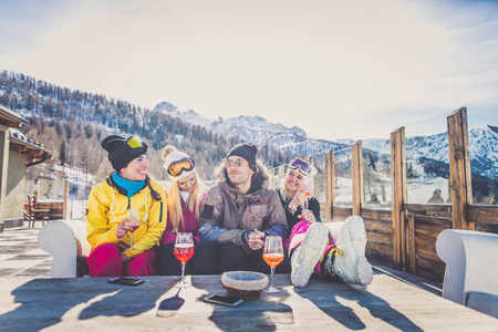 Group of friends talking and having fun in a outdoor restaurant on winter holidays 写真素材