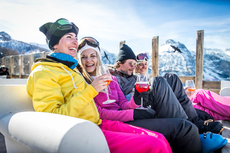 Group of friends talking and having fun in a outdoor restaurant on winter holidays Archivio Fotografico