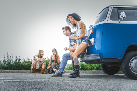 Group of friends travelling with a vintage minivan - Hippies driving into the nature