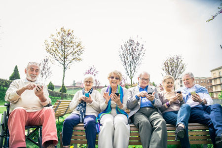Group of senior people learning to use modern technologies - Mature seniors sitting on bench in a park and staring at cellphones