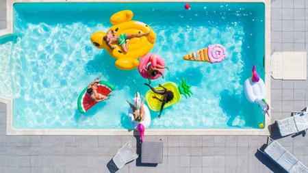 Gente felice che fa festa in un'esclusiva piscina con tappeti a forma di animali e di frutta, vista dall'alto Archivio Fotografico - 93312130