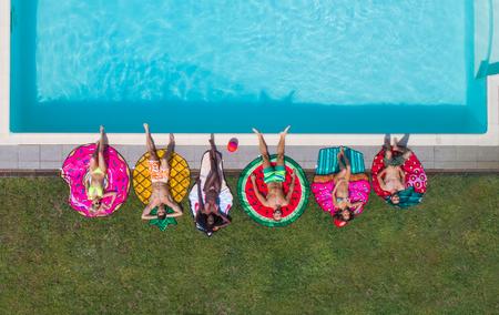 행복 한 사람들이 동물 및 과일 모양 매트와 독점적 인 수영장에서 파티, 위에서 볼 스톡 콘텐츠