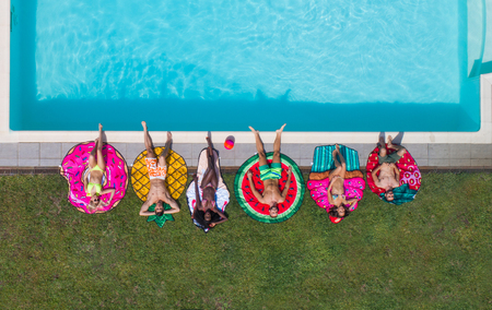Happy people partying in an exclusive swimming pool with animal and fruit shapes mats, view from above Foto de archivo - 93308159