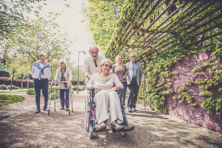 Group of senior people with some diseases walking outdoors - Mature group of friends spending time together Stock Photo