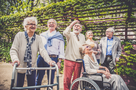Group of senior people with some diseases walking outdoors - Mature group of friends spending time together Stockfoto