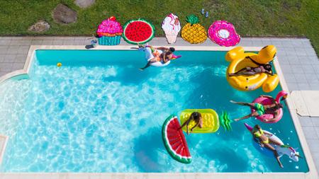 Gelukkige mensen feesten in een exclusief zwembad met matten van dieren en fruit, van bovenaf bekijken