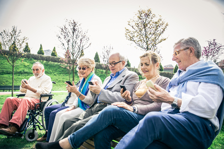 Group of senior people learning to use modern technologies - Mature seniors sitting on bench in a park and staring at cellphones Stock Photo - 93331141