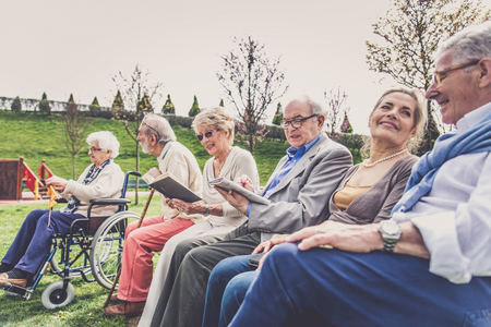 Group of senior people with some diseases walking outdoors - Mature group of friends spending time together Banco de Imagens