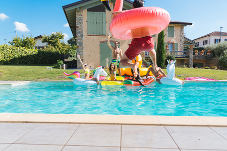 Multiracial group of friends having party in a private villa with swimming pool - Happy young people chilling with shaped air mattresses